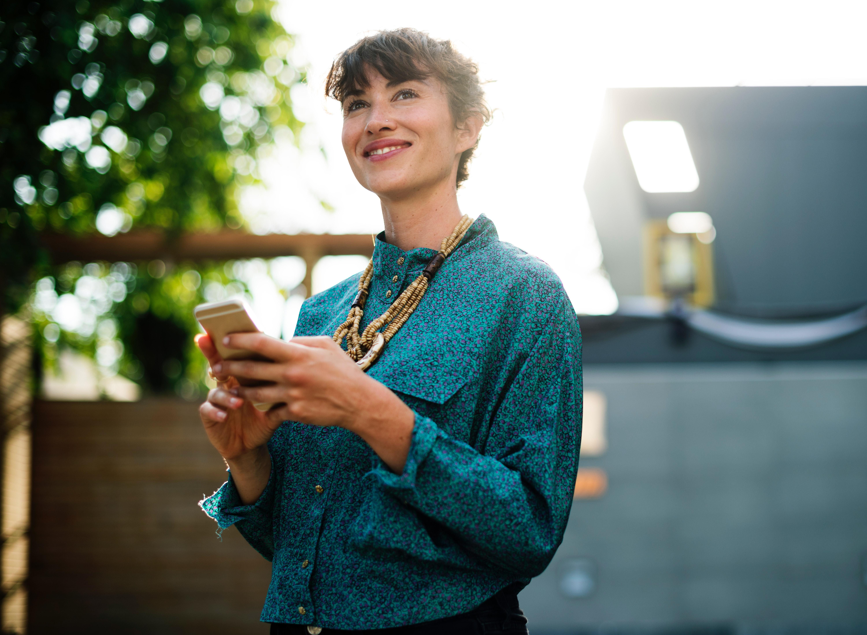 mulher utilizando imobiliária digital pelo celular